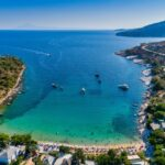 Aerial View of the Aliki Beach with colorful umbrellas, at Thassos island, Greece