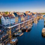 Beautiful historical city center. Nyhavn New Harbour canal and entertainment district in Copenhagen, Denmark. The canal harbours many historical wooden ships. Aerial view from the top.