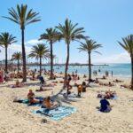 People sunbathing on the beach of El Arenal town