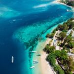 Tropical island with beach, boats and turquoise crystal ocean, aerial view. Gili islands