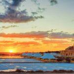 Sunset at Windmill in salt evoporation pond in Marsala Sicily