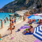 Crowd of tourists on Cala Mariolu beach in Orosei Golf, Sardinia, Italy
