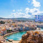 Panoramic view of Pigadia bay, town and harbor with Greek flag, Karpathos Island, Greece