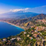Taormina is a city on the island of Sicily, Italy. Mount Etna over Taormina cityscape, Messina, Sicily. View of Taormina located in Metropolitan City of Messina, on east coast of Sicily island, Italy.
